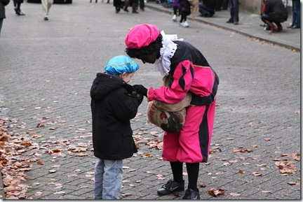 A Black Pete giving candy to a child